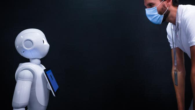 Seorang pria yang memakai masker melihat ke arah robot Pepper di SoftBank Robotics di Paris, Prancis (10/9/2020). Dengan fitur baru, robot Pepper mampu mendeteksi apakah orang-orang memakai masker, dan jika ada yang tidak memakai masker, dia akan memerintahkan mereka untuk memakainya. (Xinhua/Aureli