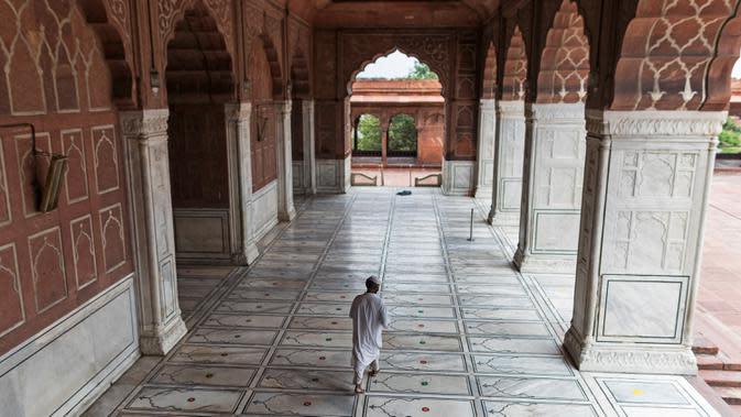 Pengurus berjalan seusai menempelkan stiker jaga jarak di lantai Masjid Jama yang dibuka kembali setelah pelonggaran lockdown di kawasan Kota Tua Delhi, Selasa (7/7/2020). India pada 6 Juli menjadi negara dengan jumlah virus corona tertinggi ketiga di dunia. (XAVIER GALIANA/AFP)