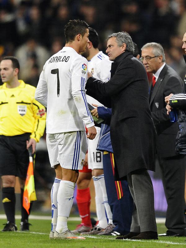 Pelatih Real Madrid Jose Mourinho (kanan) berbicara dengan penyerang Cristiano Ronaldo selama bertandign melawan Sevilla pada La Liga Spanyol di stadion Santiago Bernabeu pada 19 Desember 2010. (AFP/Pierre-Philippe Marcou)