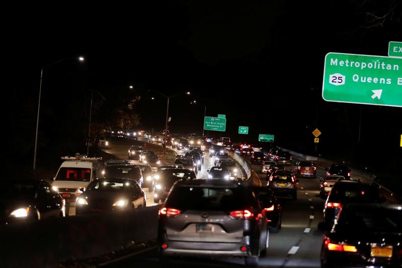 Lights illuminate the roadway as cars sit in traffic to depart New York City the day before the Thanksgiving holiday in New York