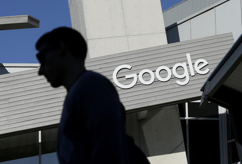 FILE - In this Nov. 12, 2015, file photo, a man walks past a building on the Google campus in Mountain View, Calif. Google said state-based hackers have targeted the campaigns of both President Donald Trump and former Vice President Joe Biden, although it saw no evidence that the phishing attempts were successful. The company confirmed the findings after the director of its Threat Analysis Group, Shane Huntley, disclosed the attempts Thursday, June 4, 2020, on Twitter. (AP Photo/Jeff Chiu, File)