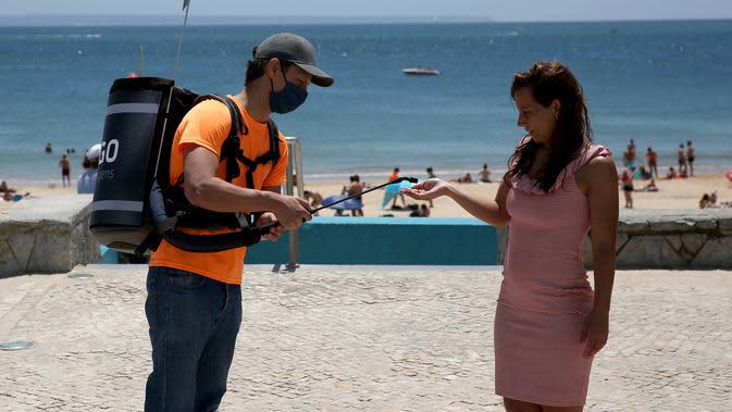 Seorang pria membagikan gel pembersih tangan di Pantai Torre, Oeiras, Lisbon, Portugal (6/6/2020). Presiden Marcelo Rebelo de Sousa dan PM Antonio Costa mengimbau rakyat Portugal agar
