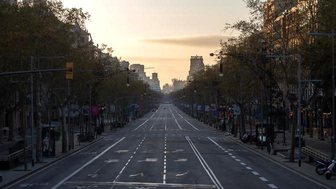 Sebuah jalan terlihat kosong di Barcelona, Spanyol, Minggu (15/3/2020). Pandemi virus corona COVID-19 membuat pemerintah Spanyol memberlakukan lockdown mulai 14 Maret 2020. (AP Photo/Joan Mateu)