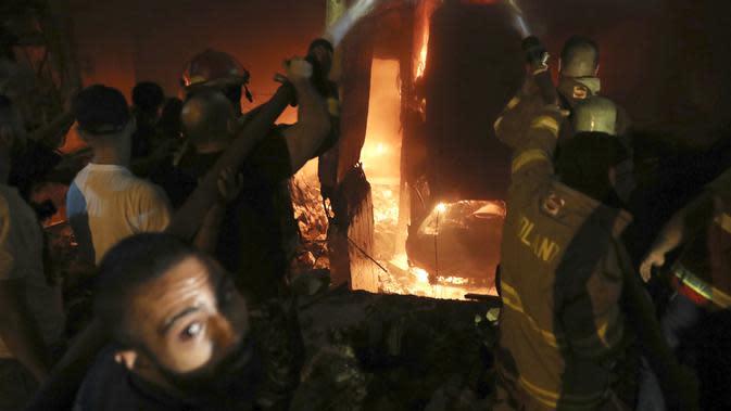 Petugas pemadam kebakaran memadamkan api di sebuah gedung setelah tangki bahan bakar meledak di lingkungan Tariq al-Jdide di Beirut (9/10/2020) waktu setempat. Ledakan terjadi usai sebuah tangki BBM terbakar di distrik Tariq al-Jdide, Sabtu (10/10/2020). (AP Photo/Bilal Hussein)