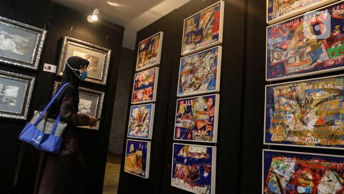 Pengunjung mengamati pameran seni rupa yang bertajuk 'Creative Freedom to Heal The Nation' di Perpustakaan Nasional, Jakarta, Kamis (15/10/2020). Pameran ini diharap dapat mendukung pemerintah dalam menanamkan kesadaran disiplin kepada masyarakat dalam menyikapi pandemi. (Liputan6.com/Johan Tallo)