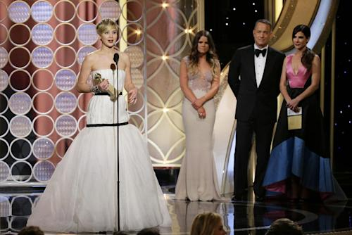 """This image released by NBC shows Jennifer Lawrence, left, accepting the award for best supporting actress in a motion picture for her role in """"American Hustle,"""" as presenters Sandra Bullock, right, and Tom Hanks, second right, look on during the 71st annual Golden Globe Awards at the Beverly Hilton Hotel on Sunday, Jan. 12, 2014, in Beverly Hills, Calif. (AP Photo/NBC, Paul Drinkwater)"""