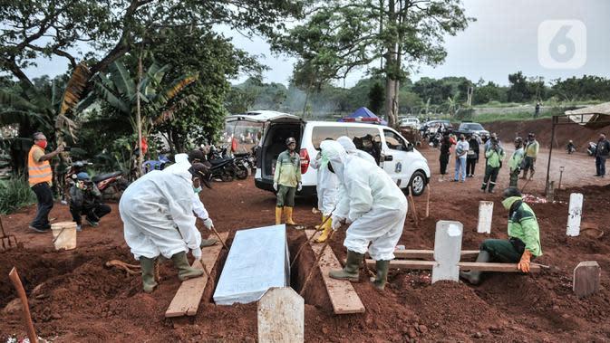 Petugas mengenakan alat pelindung diri dan baju hazmat saat proses pemakaman protap Covid-19 di TPU Pondok Ranggon, Jakarta, Senin (28/9/2020). (merdeka.com/Iqbal S. Nugroho)