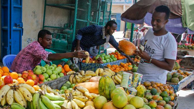 Seorang pelanggan memeriksa buah di pasar jalanan ketika keluarga berbelanja untuk liburan Muslim Idul Fitri, yang menandai akhir bulan puasa Ramadhan, di Mogadishu, Somalia, (19/5/2020). (AP Photo/Farah Abdi Warsameh)