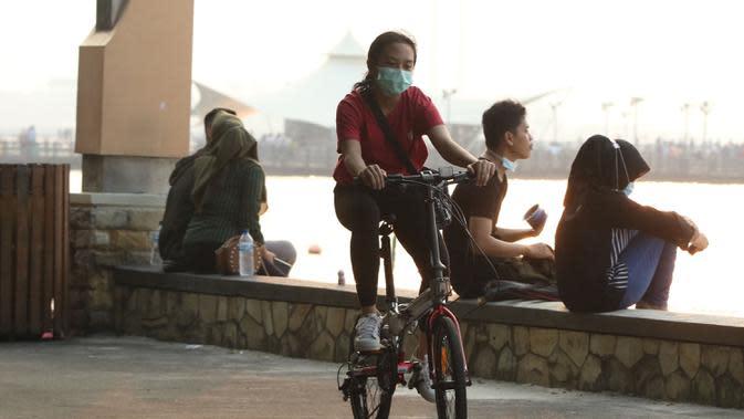 Pengunjung menikmati suasana Pantai Ancol, Jakarta, menjelang berlakunya PSBB, Sabtu (12/9/2020). Pemprov DKI berencana menutup sejumlah tempat rekreasi di antaranya Ancol, Ragunan, Monas, dan Taman Mini Indonesia Indah saat PSBB total pada 14 September mendatang. (Liputan6.com/Herman Zaharia)