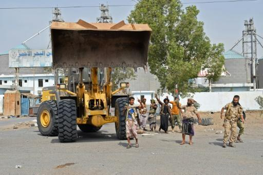 Yemeni pro-government fighters use bulldozers to smash though rebel defences as they advance towards Hodeida's vital docks