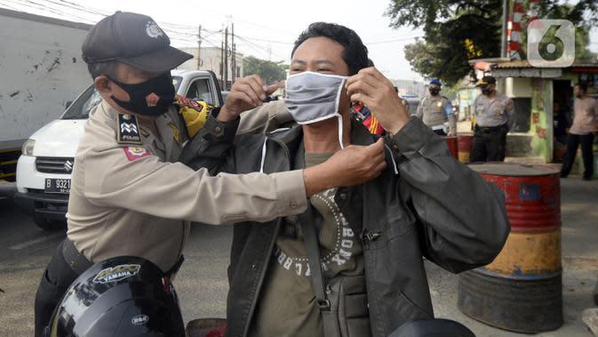 Anggota polisi dari Polsek Parung membantu memasangkan masker kepada pengendara sepeda motor di depan Polsek Parung, Kabupaten Bogor, Jawa Barat, Rabu (2/9/2020). Pembagian masker gratis setiap usai apel ini inisiatif anggota sejak masa pandemi COVID-19. (merdeka.com/Dwi Narwoko)