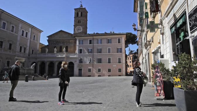 Warga melakukan social distancing atau menjaga jarak saat akan memasuki apotek di Roma, Italia, Senin (16/3/2020). Social distancing adalah cara terbaik untuk mencegah penyebaran virus corona COVID-19. (AP Photo/Alessandra Tarantino)