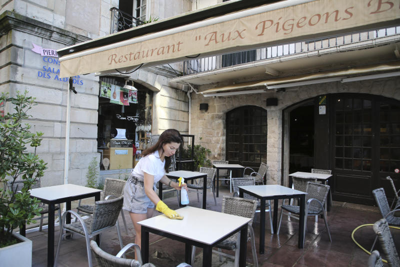 A restaurant employee Annabelle Mathis cleans a table in a restaurant of Saint-Jean-de-Luz, southwestern France, Friday May 29, 2020. From June 2 restaurants and cafes will reopen, together with monuments and museums, concert halls and theaters, beaches, campsites, gyms and public swimming pools. There's a notable exception for the Paris region, the country's worst-affected by the virus, where many facilities will have to wait until June 22 to reopen. (AP Photo/Bob Edme)
