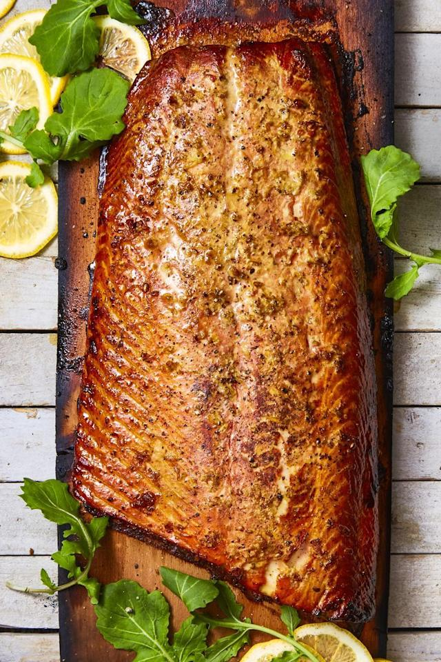 """<p>Basted in soy sauce, honey, and sriracha, this grilled salmon gets another flavorful edge from the cedar plank it is roasted on. If you're <a href=""""https://www.goodhousekeeping.com/food-recipes/g605/family-style-recipes/"""" target=""""_blank"""">feeding a larger crowd</a>, this fish recipe is for you.<br></p><p><em><a href=""""https://www.goodhousekeeping.com/food-recipes/a44681/honey-ginger-cedar-plank-salmon-recipe/"""" target=""""_blank"""">Get the recipe for Honey-Ginger Cedar Plank Salmon »</a></em></p>"""