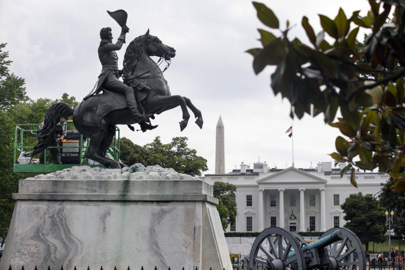 With the White House and the Washington Monument in the background, a National Park Service worker cleans a statue of President Andrew Jackson, Thursday, June 11, 2020, near the White House in Washington, after protests over the death of George Floyd, a black man who was in police custody in Minneapolis. Floyd died after being restrained by Minneapolis police officers. (AP Photo/Jacquelyn Martin)