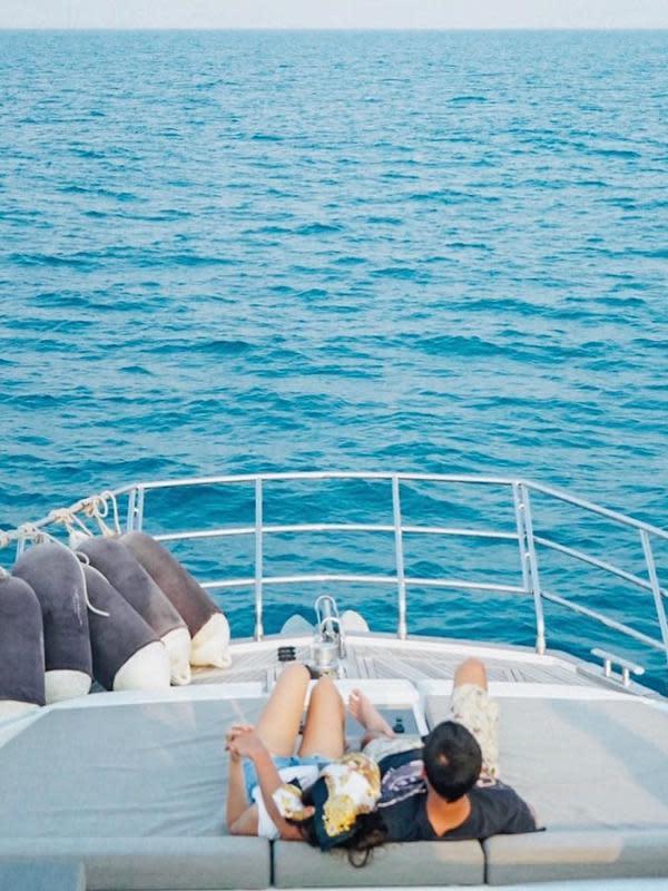 Potret kemesraan Alyssa dan Al Ghazali di atas kapal. Pasangan yang telah menjalin hubungan beberapa tahun itu terlihat memandang ke arah depan lautan biru air laut. (Instagram/alyssadaguise)
