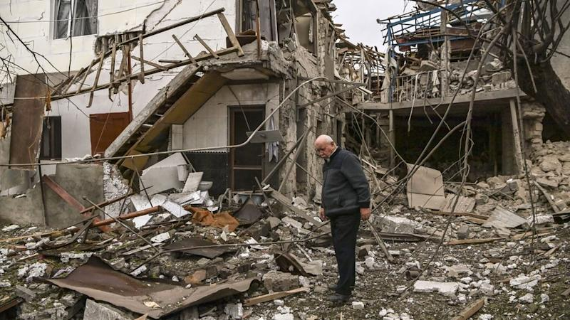 An elderly man stands in front of a destroyed house after shelling in the breakaway Nagorno-Karabakh region`s main city of Stepanakert