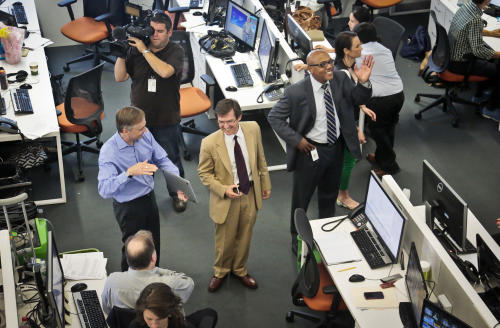 Paul Eedle, center, deputy launch manager for Al-Jazeera America, reacts as he looks at a tablet while making last minute rounds with editorial staff just before the network's first broadcast on Tuesday, Aug. 20, 2013 in New York. The Qatar-based Al-Jazeera Media Network launched its U.S. outlet only eight months after announcing the new venture, which on Tuesday replaced Al Gore's Current TV in more than 45 million TV homes. (AP Photo/Bebeto Matthews)