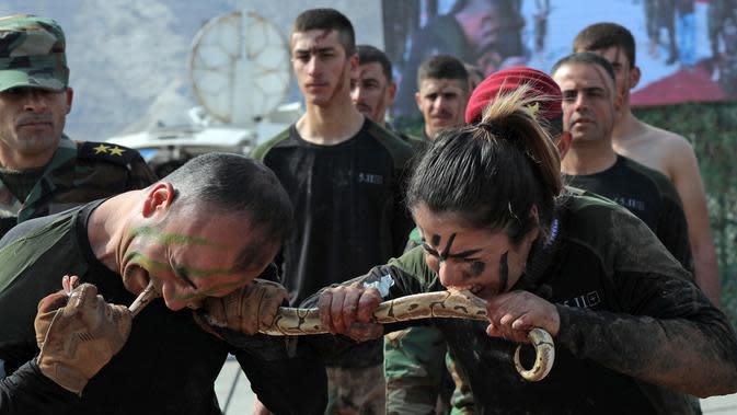 Pasukan perempuan Peshmerga bersama seorang pria menggigit ular saat berlatihan dalam upacara kelulusan di Kota Soran, Irak, Rabu (12/2/2020). Latihan militer pasukan bersenjata Kurdi tersebut dilakukan sekitar 100 kilometer timur laut ibu kota otonomi wilayah Kurdi di Irak, Arbil. (SAFIN HAMED/AFP)
