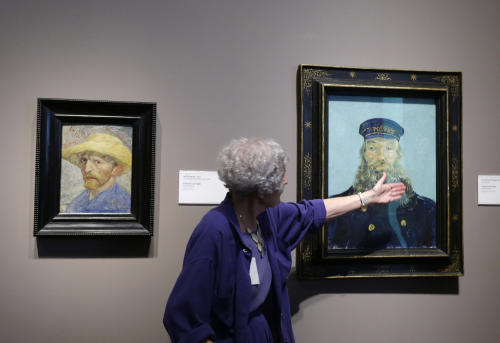 FILE - In a June 13, 2013 file photo, Detroit Institute of Arts docent Lea Schelke points out details in the Portrait of Postman Roulin by Van Gogh displayed at the museum in Detroit. As part of the city's Chapter 9 bankruptcy filing, city emergency manager Kevyn Orr said Monday, Aug. 5, 2013, that he has asked the Christie's auction house to appraise the museum's collection, raising the possibility it could be put up for sale. (AP Photo/Carlos Osorio, File)