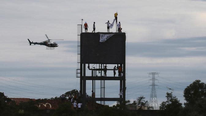 Helikopter polisi militer mengitari Penjara Puraquequara saat narapidana melakukan protes dengan menaiki menara air, Manaus, Brasil, Sabtu (2/5/2020). Mereka memprotes kondisi buruk dan pemberlakuan pembatasan kunjungan keluarga untuk mencegah penyebaran corona COVID-19. (AP Photo/Edmar Barros)