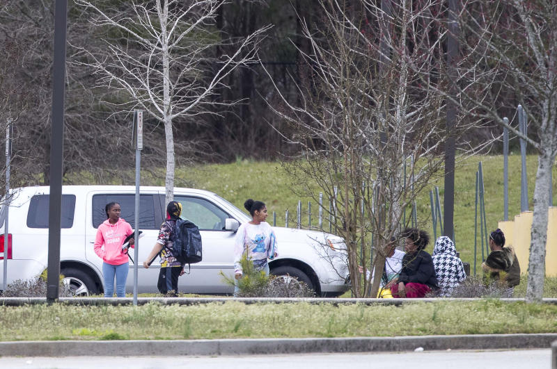 Students wait outside at Woodland Middle School in East Point, Ga., Monday, March 9, 2020. The Fulton County School system has decided to close schools on Tuesday after a teacher tested positive with the coronavirus. The teacher was at Woodland Middle school on Friday. (Alyssa Pointer/Atlanta Journal-Constitution via AP)