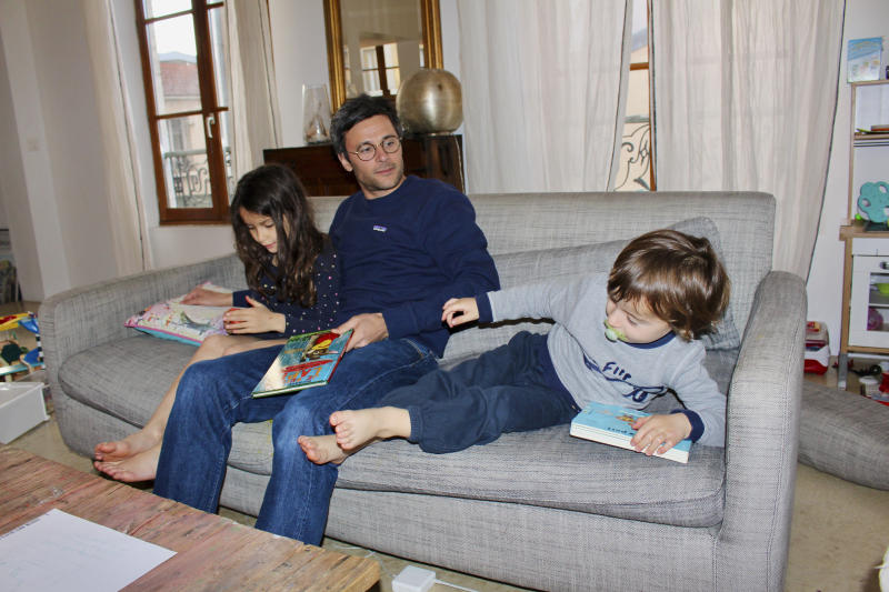 In this photo taken Thursday April 30, 2020 Kimkhi Nguyen plays on a sofa with his children Mila, 7, and Andre, 3, in Paris. As France prepares to start letting public life resume after eight weeks, many parents are deeply torn over a question without a clear or conclusive answer: Should I send my child back to school?  The French government is easing some of the closure and home-confinement orders it imposed March 17 to curb coronavirus infections, with businesses permitted to reopen, residents cleared to return to workplaces and schools welcoming some students again starting Monday.  (AP Photo/Oleg Cetinic)