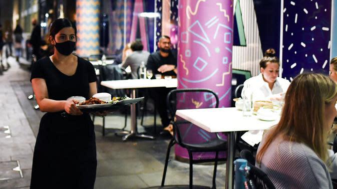Pramusaji mengenakan masker saat melayani pelanggan di luar restoran di Soho, London, Selasa (22/9/2020). Perdana Menteri Inggris, Boris Johnson, telah mengumumkan bahwa pub dan restoran tutup pada pukul 10 malam, karena lonjakan kasus virus corona di seluruh Inggris. (AP Photo / Alberto Pezzali)