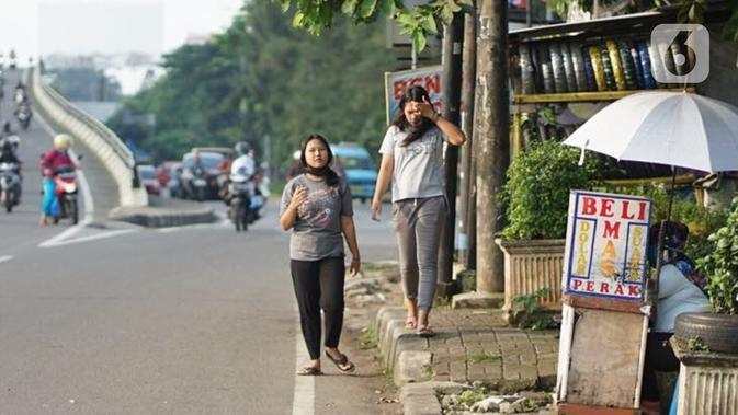 Pejalan kaki tanpa mengenakan masker melintas di Kawasan Jakarta, Selasa (19/5/2020). Sanksi PSBB yang kurang tegas menyebabkan sebagian warga masih bebas beraktivitas tanpa menggunakan masker, meskipun resiko penyebaran virus corona masih tinggi. (Liputan6.com/Immanuel Antonius)