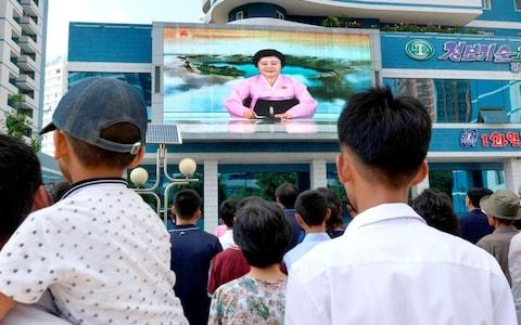 North Koreans watch a news report showing North Korea's nuclear test on electronic screen in Pyongyang  - Credit: KYODO