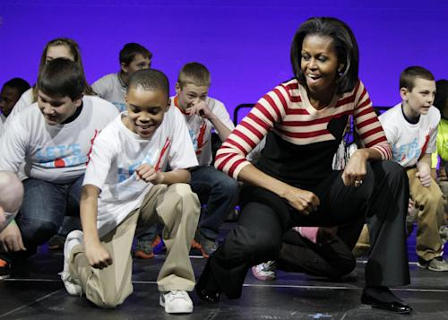 """FILE - In this Feb. 9, 2012 file photo, First lady Michelle Obama does the Interlude dance with kids on stage during a Let's Move event with children from Iowa schools, at the Wells Fargo Arena in De Moines, Iowa, during her three day national tour celebrating the second anniversary of Let's Move. Nearing a milestone birthday, Michelle Obama describes herself as """"50 and fabulous."""" She's celebrating already and a big birthday bash is in the works. (AP Photo/Carolyn Kaster)"""