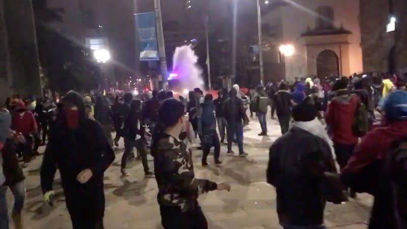 Demonstrator gestures towards riot police in Bogota