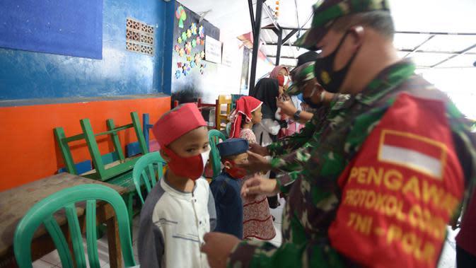 Tentara membagikan masker kepada warga RW 11, Kelurahan Pondok Kopi, Jakarta, Jumat (18/9/2020). Di masa pandemi COVID-19, TNI dan Polri bersinergi mengimbau warga untuk mematuhi protokol kesehatan dengan memakai masker saat beraktivitas di luar rumah. (merdeka.com/Imam Buhori)