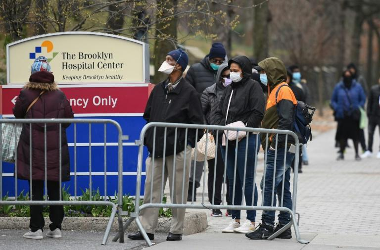 People who believe they have COVID-19, and who meet the criteria, wait in line to be pre-screened for the coronavirus outside of the Brooklyn Hospital Center