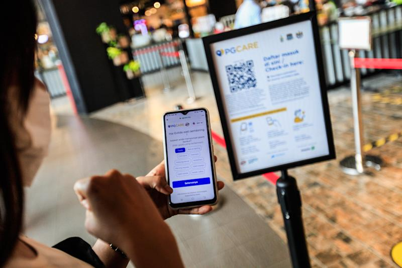 Members of the public are pictured using the PGCare app at the Queensbay Mall in Penang May 18, 2020. — Picture by Sayuti Zainudin