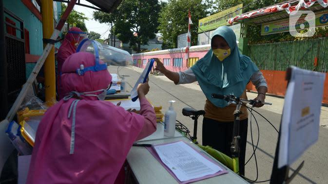 Guru SDIT Ibnu Sina memberikan tugas sekolah secara drive-thru kepada wali murid di Jakarta, Rabu (26/8/2020). Tugas sekolah tersebut dikerjakan oleh siswa dalam satu minggu agar penilaian dan proses belajar mengajar tetap berlangsung. (merdeka.com/Imam Buhori)