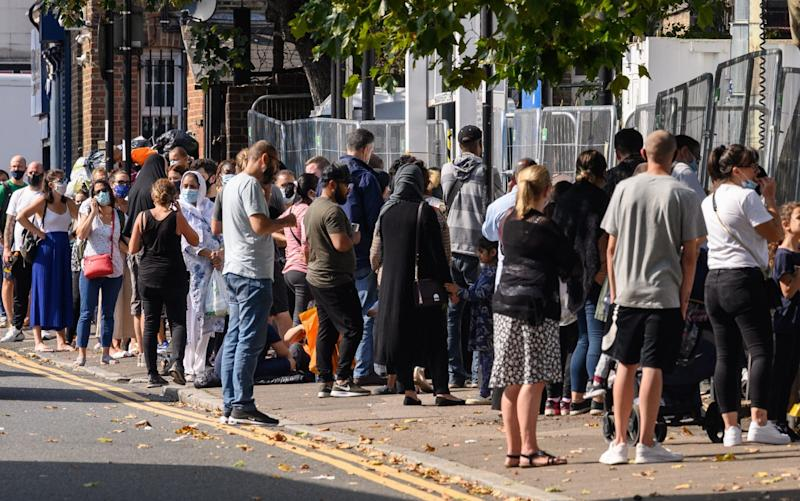 Queues stretch along the pavement at a walk-in Covid-19 testing centre in London - Getty Images Europe