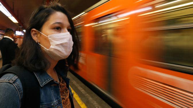 Seorang wanita mengenakan masker menunggu kereta di Mexico City (23/3/2020). Pemerintah kota mengumumkan langkah-langkah untuk menangani COVID-19 seperti menutup bar, disko, museum, kebun binatang, bioskop, teater dan gym mulai Senin. (AP Photo/Marco Ugarte)