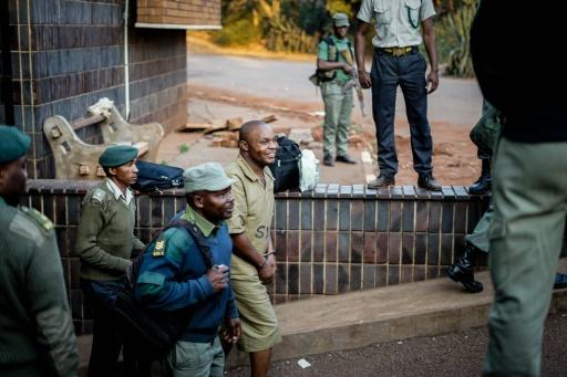 A supporter of the Movement for Democratic Change (MDC) opposition party is escorted to a prison truck outside the magistrate's court in Harare on August 6, 2018 after 27 were arrested over alleged links to post-election violence