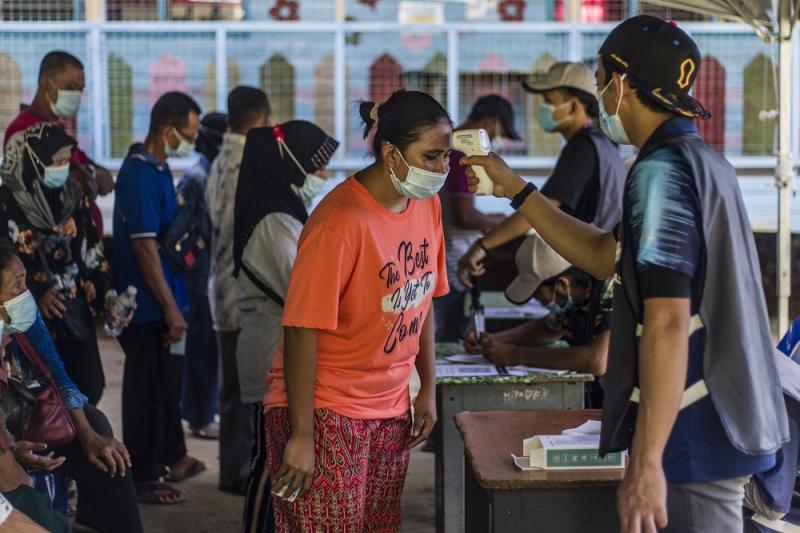 Voters get their temperatures checked before heading to the polling booths to cast their votes at SK Pulau Gaya September 26, 2020.