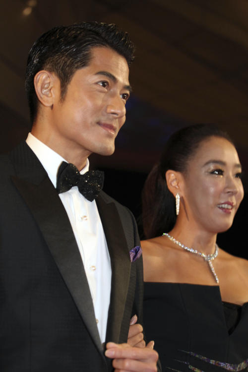FILE - In this Thursday, Oct. 3, 2013 file photo, Chinese actor Aaron Kwok and South Korean actress Kang Soo-yeon arrive at the opening ceremony of the Busan International Film Festival at Busan Cinema Center in Busan, south of Seoul, South Korea. What would be the price for hiring Asia's biggest movie stars to host the region's largest film event? Kwok opened this year's Busan International Film Festival for mere 500,000 won or $465, according to Yang Heon Kyu, who oversees the festival's budget. The goodwill of big-name stars is one indication of how important Busan has become to the Asian film industry in less than two decades. (AP Photo/Woohae Cho, File)