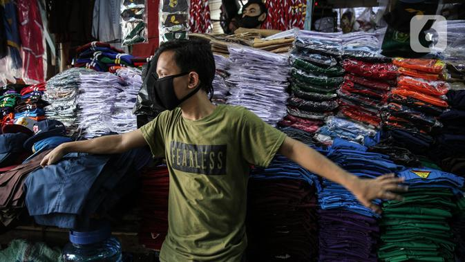 Penjual seragam sekolah menunggu pembeli di kawasan Pasar Jatinegara, Jakarta, Selasa (30/6/2020). Sejumlah pedagang di tempat itu mengeluhkan omset penjualan seragam sekolah yang menurun hingga 90 persen akibat sepi pembeli dan anjuran belajar di rumah saat COVID-19. (Liputan6.com/Faizal Fanani)
