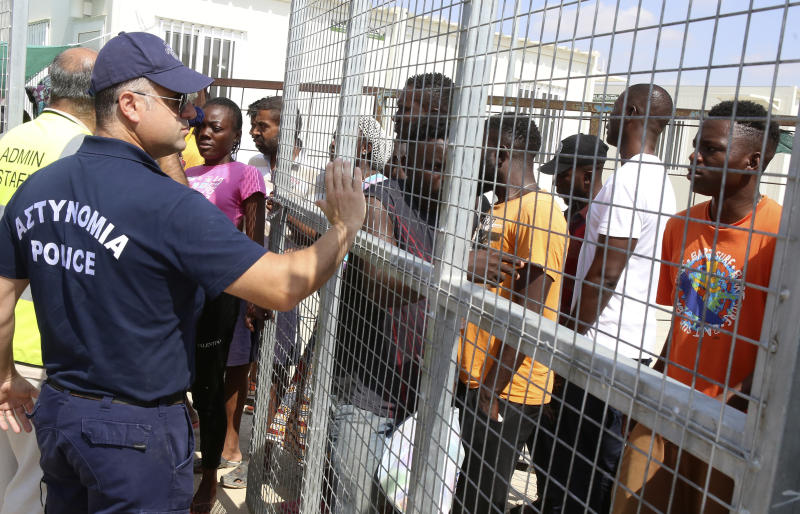 A police officer stands guard as migrants stand inside a refugee camp in Kokkinotrimithia outside of Nicosia, Cyprus, on Tuesday, June 23, 2020. Cyprus' interior minister says he has asked police to launch a criminal probe into allegations that underage girls staying at a migrants' reception center were sexually harassed by other adults staying there. (AP Photo/Philippos Christou)