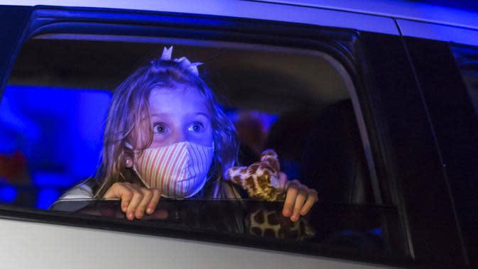 Seorang anak yang mengenakan masker menonton pertunjukan dari dalam mobil di taman hiburan horor Hopi Hari, pinggiran Vinhedo, Sao Paulo, Brasil, Jumat (4/9/2020). Karena pembatasan akibat COVID-19, taman hiburan horor Hopi Hari menampilkan pertunjukan secara drive-thru. (AP Photo/Carla Carniel)