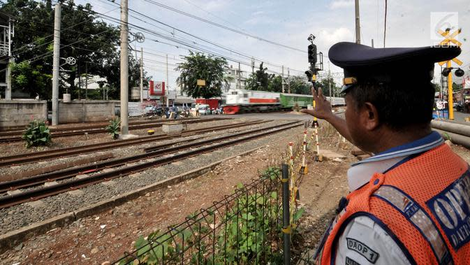 Seorang petugas berjaga di perlintasan kereta api Nomor 52 di Pisangan Lama, Jakarta, Kamis (11/4). Pintu perlintasan ini dan JPL 66 di Jalan Stasiun Cakung, Jakarta Timur, akan ditutup permanen saat diberlakukannya Double Double Track (DDT) lintas Manggarai-Cikarang. (merdeka.com/Iqbal S. Nugroho)