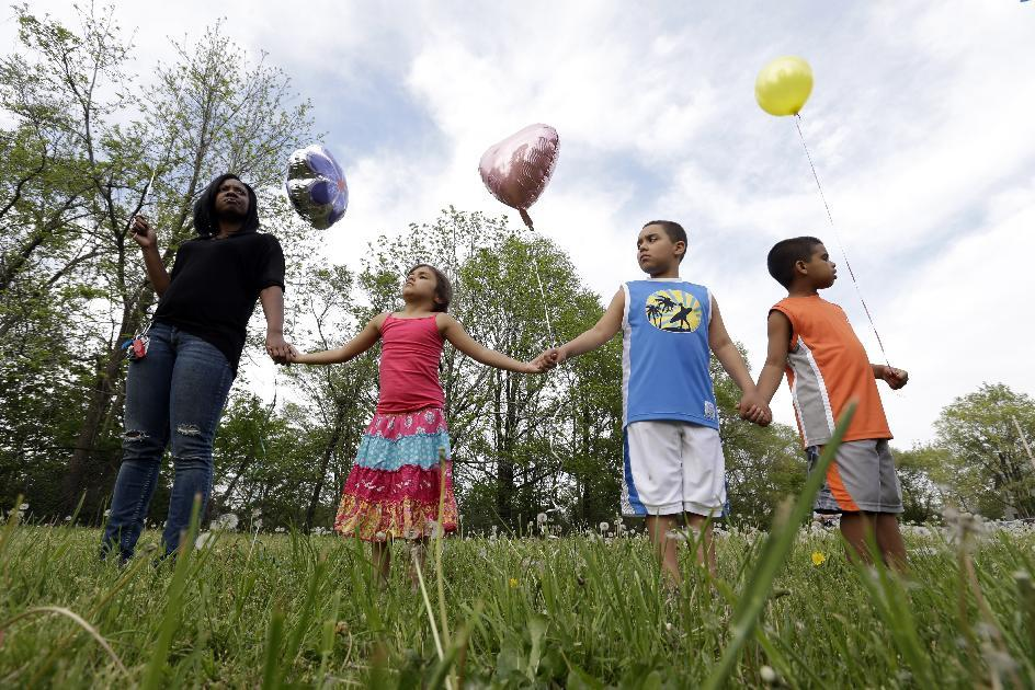 Residents listen to speeches before  releasing balloons in support of the three women found in a house on Seymour Avenue in Cleveland, Ohio, Thursday, May 9, 2013. Prosecutors said Thursday they may seek the death penalty against Ariel Castro, the man accused of imprisoning three women at his home for a decade, as police charged that he impregnated one of his captives at least five times and made her miscarry by starving her and punching her in the belly. (AP Photo/David Duprey)