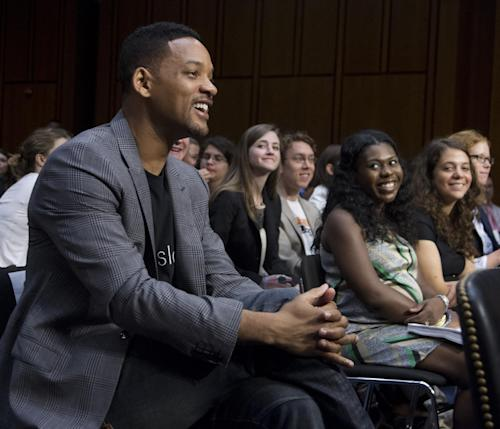 """Actor Will Smith, accompanying his wife Jada Pinkett Smith, not in picture, smiles as he is acknowledged in the hearing room by committee Chairman Sen. John Kerry, D-Mass., during a Senate Foreign Relations Committee on """"The Next Ten Years in the Fight Against Human Trafficking: Attacking the Problem with the Right Tools"""" on Capitol Hill in Washington Tuesday, July 17, 2012. (AP Photo/Manuel Balce Ceneta)"""