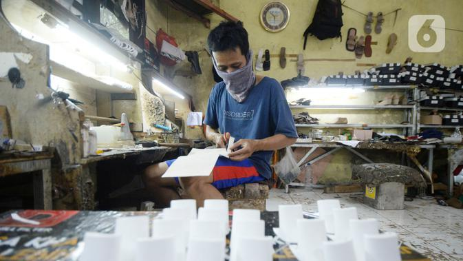 Pekerja sedang menyelesaikan produksi home industri sepatu wanita pesanan pembeli di Pamulang, Tangerang Selatan, Banten, Rabu (14/10/2020). Pada masa pandemi ini pemesanan sepatu turun 40 persen dibandingkan sebelum Covid-19. (merdeka.com/Dwi Narwoko)
