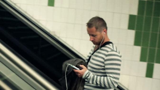 Ilustrasi bermain ponsel di eskalator
