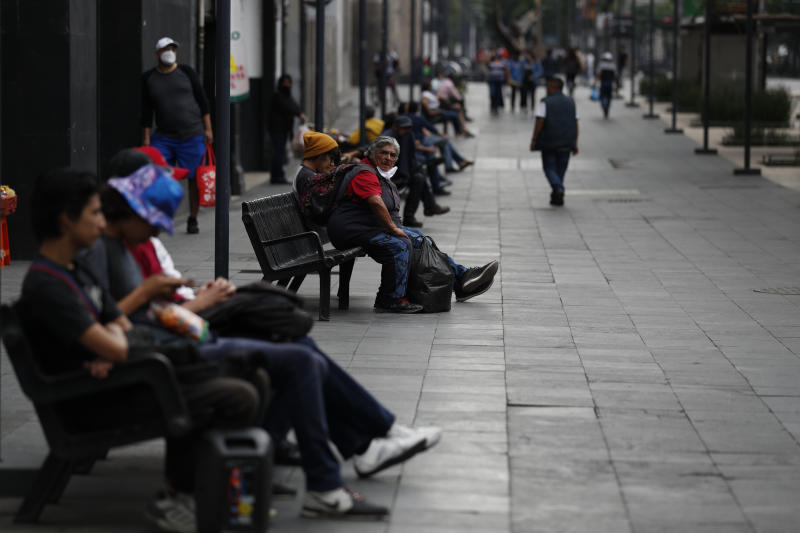 "People enjoy the fresh air on benches along Juarez Avenue in central Mexico City, Sunday, May 31, 2020. Mexico's capital plans to reopen certain sectors of the economy and public life beginning Monday, despite the city still being in the most serious ""red light"" phase of the coronavirus pandemic. (AP Photo/Rebecca Blackwell)"